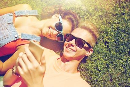 Junges Mädchen und junger Mann liegen auf dem Rasen und betrachten im Smartphone